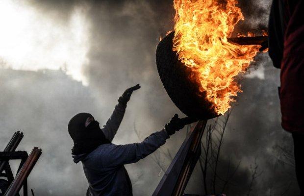 Un manifestant antigouvernemental lançant un pneu enflammé sur la place de l'Indépendance, à Kiev, le 21 février 2014. Bülent Kiliç / AFP.