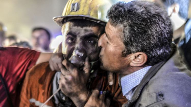 "A man kisses his son, rescued of the mine, on May 13, 2014 after an explosion in a coal mine in Manisa. At least 157 miners were killed in collapsed coal mine in the western Turkish city of Manisa. ""At least 200-300 workers were working in the mine when an electric fault caused an explosion,"" the mayor of Soma, a district of Manisa, told private NTV television. AFP PHOTO/BULENT KILIC"